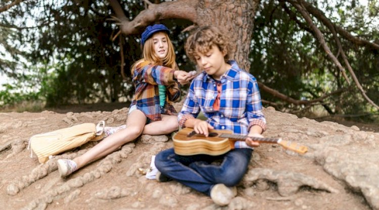 A boy and a girl playing the guitar.